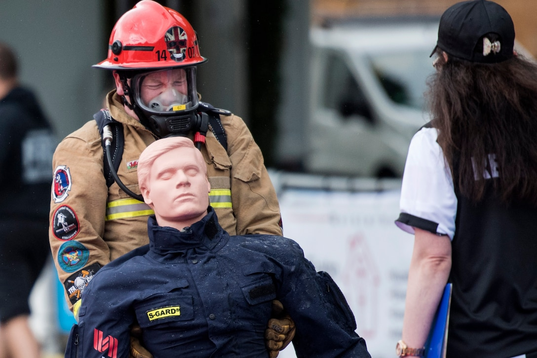 A firefighter from Great Britain carries a dummy while racing against an opponent and the clock during the 4th annual Mosel Firefighter Combat Challenge in Ediger-Eller, Germany, June 30, 2017. The last obstacle of the event involved carrying a 175 pound dummy 106 feet to the finish line. (U.S. Air Force photo by Senior Airman Preston Cherry)