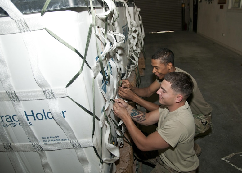 Pfc. Noah Buckhouse and Spc. John Caulder of the 824th Quartermaster Company, secure a container with cargo netting for aerial delivery at Al Udeid Air Base, Qatar on April 25, 2017. Aerial delivery operations are essential for getting supplies to troops in the Middle East when conventional means of transportation are not feasible. (U.S. Army photo by Sgt. Jeremy Bratt)