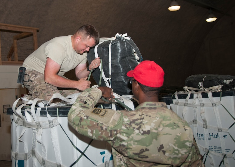 Spc. Alexander Triska and Spc. Keith Manning of the 824th Quartermaster Company, secure a parachute to a container for aerial delivery at Al Udeid Air Base, Qatar on April 25, 2017. Aerial delivery operations are essential for getting supplies to troops in the Middle East when conventional means of transportation are not feasible. (U.S. Army photo by Sgt. Jeremy Bratt)