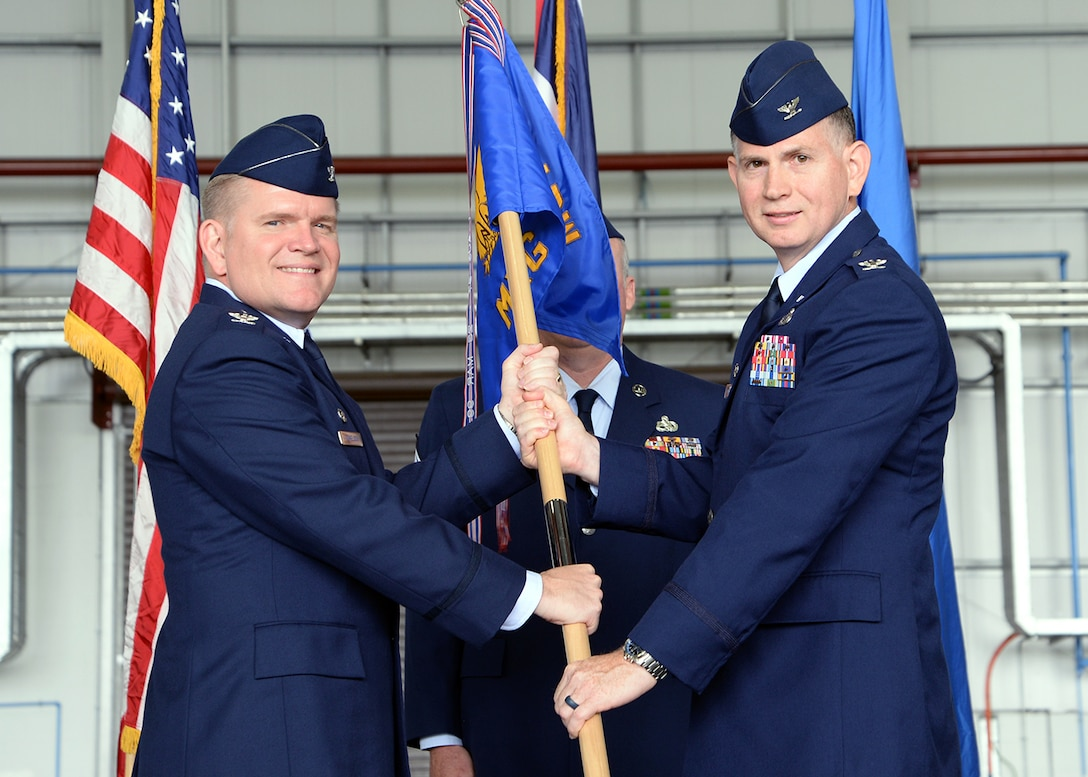 U.S. Air Force Col. Thomas D. Torkelson, left, 100th Air Refueling Wing commander, passes the guidon to U.S. Air Force Col. Matthew Pollock, 100th Maintenance Group commander, July 6, 2017, during a change of command ceremony on RAF Mildenhall, England. The ceremony is a time-honored tradition in which one officer relinquishes command and passes it to another. (U.S. Air Force photo by Karen Abeyasekere)