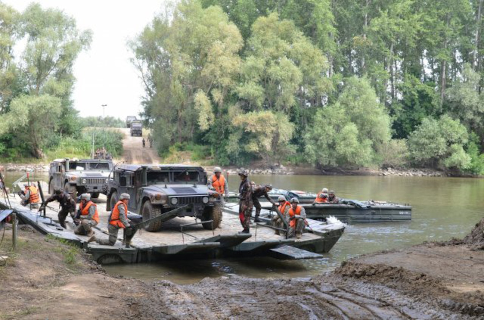 GYOR, Hungary - Military vehicles belonging to 1st squadron, 2nd Cavalry Regiment, Vilseck, Germany, are ferried over the Danube River during a rehearsal river crossing at Gyor, July 4. The ferry is employed by 837th Brigade Engineer Battalion, Ohio National Guard, and 37th Engineer Regiment, Hungarian Ground Forces. The exercise, Szentes Axe, a Hungarian-led exercise under Saber Guardian, facilitates the freedom of movement for 2nd Cavalry Regiment as the unit moves into Romania for more training with NATO Allies and partners. Saber Guardian is the largest exercise in the Black Sea Region and will take place in three countries. (U.S. Army photo by Sgt. Shiloh Capers) (Photo Credit: Sgt. Shiloh Capers)