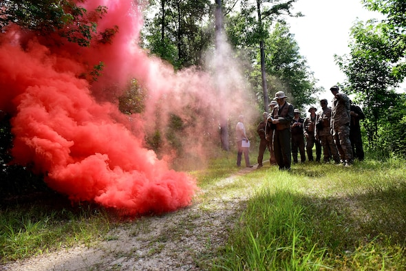 A survival, evasion, resistance and escape specialist, SERE augmentees, pilots, and weapon systems officers from Seymour Johnson Air Force Base, North Carolina, practice properly using smoke signals during a combat survival training course, June 27, 2017, at Howell Woods, Four Oaks, North Carolina. Pilots and WSO's need to retake their CST and water survival training courses every three years. (U.S. Air Force photo by Airman 1st Class Kenneth Boyton)