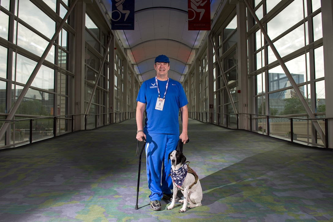 Air Force veteran Tech Sgt. Eric Fisher and his dog Lola stand for photo at McCormick Place where several events in the 2017 Dept. of Defense Warrior Games are being held in Chicago June, 29, 2017.  The DoD Warrior Games are an annual event allowing wounded, ill and injured service members and veterans to compete in Paralympic-style sports. (DoD photo by EJ Hersom)