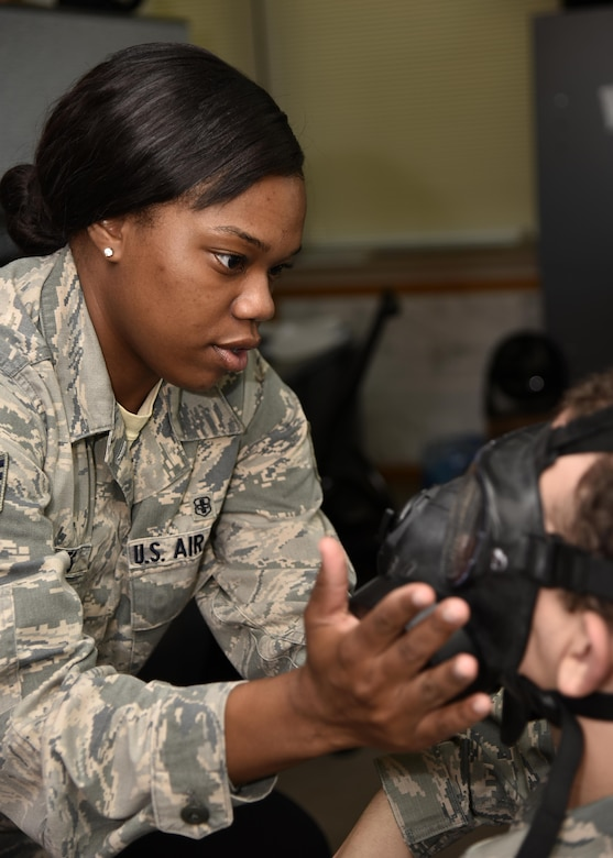 Air Force Staff Sgt. Akina L. Jones, an industrial hygiene and occupational health NCO in charge assigned to the 175th Medical Group, checks a service member's gas mask June 30, 2017, at Warfield Air National Guard Base, Md. Jones enlisted in July 2011 and has been with the Air National Guard since switching from active duty in 2015. (U.S. Air National Guard photo by Airman Sarah M. McClanahan)