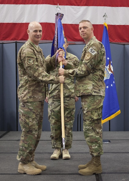 Col. John Grimm, 90th Security Forces Group commander, passes the guidon to Lt. Col. Anthony McCarty, 90th Missile Security Forces Squadron commander, during the 90th MSFS change of command ceremony July 6, 2017, as Senior Master Sgt. Rory Peters, 90th MSFS first sergeant, stands in the background on F.E. Warren Air Force Base, Wyo. The ceremony signified the transition of command from Lt. Col. James Hughes to McCarty. (U.S. Air Force photo by Lan Kim)