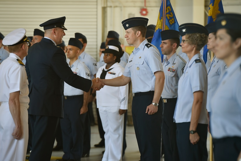 Col. Robert Lyman, left, 628th Air Base Wing and Joint Base Charleston outgoing commander, shakes the hand of Lt. Col. Bryan Collins, right, 628th Comptroller Squadron commander, during a wing inspection as part of a change of command ceremony at Nose Dock 2 here, July 6, 2017. Col. Jeffrey Nelson took command from Col. Robert Lyman, during the ceremony. U.S. Air Force Maj. Gen. Christopher Bence, U.S. Air Force Expeditionary Center commander, presided over the ceremony.