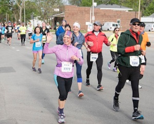 Irene Macallister of the Construction Engineering Research Laboratory waves at the 'Discount Rhythm Dukes' band in front of Second Hand Rose on Main Street in Urbana during the Ninth Illinois Marathon.