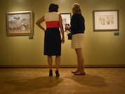Lin Ezell (right), director of the National Museum of the Marine Corps, explains the various paintings to Karen Pence  (left), second lady of the United States, in the Combat Art Gallery at the museum in Triangle, Virginia, July 6.  The works represent Marine experiences around the globe by artists who used their talents to tell the story of their fellow Marines, based in part on their own experiences and perspectives. This first exhibition will be on display through April 2018.