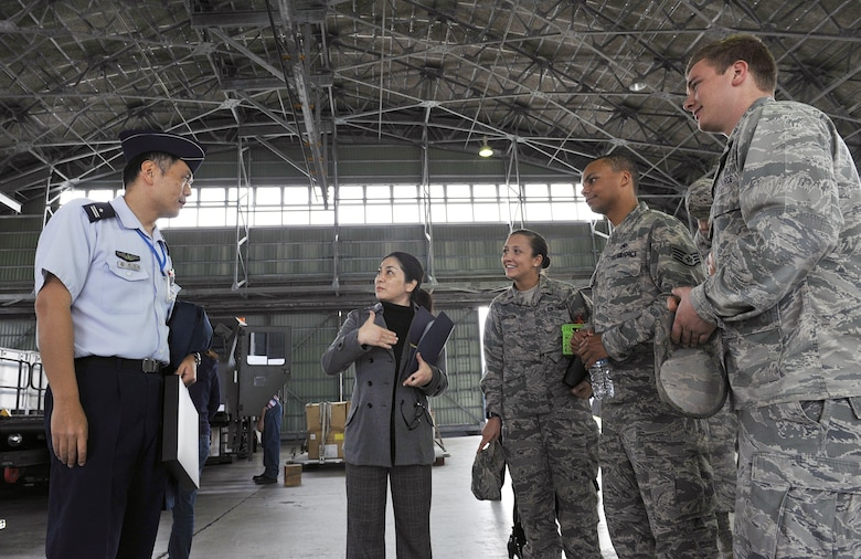 Japan Air Self Defense Force Maj. Toshiro Hatamoto, headquarters, Southwestern Composite Air Division logistic planning transportation section chief, speaks with U.S. Air Force 733rd Air Mobility Squadron members about the JASDF side of Aerial Port operations, March 10, 2016, at Naha Air Base, Japan. The 733rd AMS toured Naha Air Base to build relations between the U.S. Air Force and JASDF partners. (U.S. Air Force photo by Naoto Anazawa)