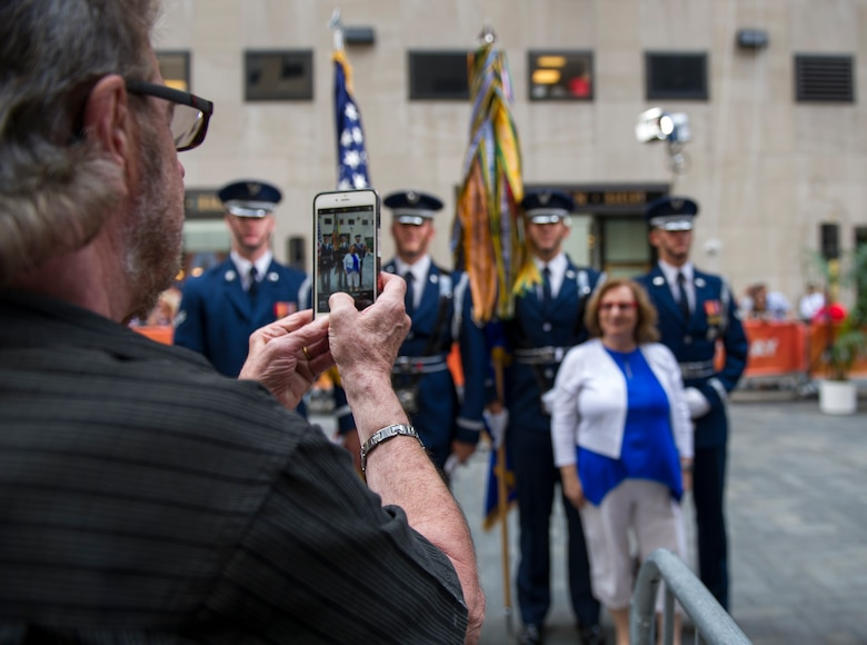 An audience member takes a photo of his wife posing with members of the U.S. Air Force Honor Guard following a taping of the Today Show in New York City, July 4, 2017. The U.S. Air Force Band ceremonial brass ensemble and Honor Guard color team were there to represent the men and women of the U.S. Air Force and spread patriotism during Independence Day celebrations on the Today Show and a New York Yankees baseball game. (US Air Force Photo by Airman 1st Class Gabrielle Spalding)