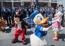 "Disney characters run in front of a U.S. Air Force Honor Guard group photo at Disneyland in Anaheim, Calif., June 29, 2017. The ""Ambassadors in Blue"" demonstrated drill routines during their recent tour of Southern California where they also performed at Sea World, Disney's California Adventure Park, and Mission Beach from June 27 to July 1. (U.S. Air Force photo by Senior Airman Jordyn Fetter)"