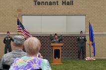 Lt. Col. Jennifer Saraceno, 97th Intelligence Squadron commander, officially unveils Tennant Hall on the squadron headquarters building during a ceremony here June 30. The facility was dedicated in honor of retired Chief Master Sgt. Thomas H. Tennant who played a major role establishing intelligence, surveillance and reconnaissance operations in multiple units which later became the 97th IS. (U.S. Air Force photo by Charles Haymond)