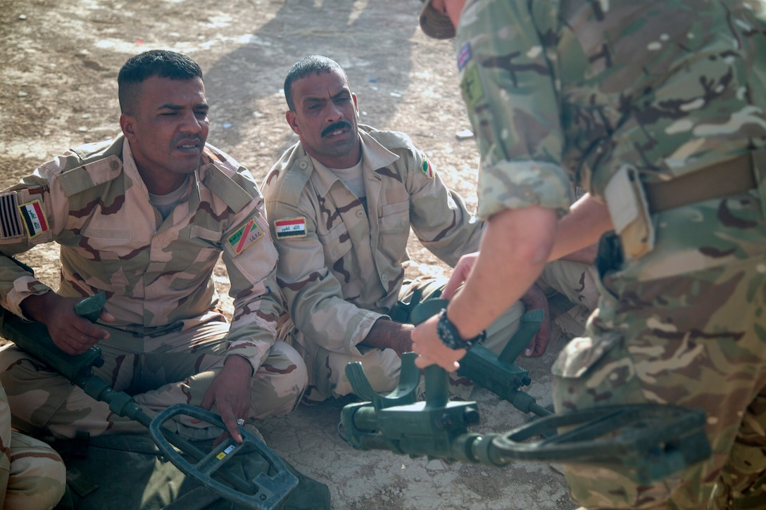 A U.K. army trainer explains the parts of the Vallon metal detector during mine detection training at the Besmaya Range Complex Iraq, July 2, 2017. This training is part of the overall Combined Joint Task Force - Operation Inherent Resolve building partner capacity mission which focuses on training and improving the capability of partnered forces fighting ISIS. CJTF-OIR is the global Coalition to defeat ISIS in Iraq and Syria. (U.S. Army photo by Cpl. Tracy McKithern)