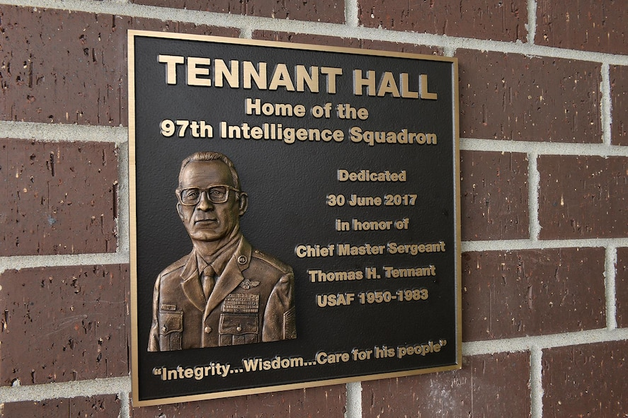 A plaque highlighting the career of retired Chief Master Sgt. Thomas H. Tennant is on display at Tennant Hall, the home of the 97th Intelligence Squadron here. The facility was dedicated to Tennant during a ceremony on June 30. (U.S. Air Force photo by Charles Haymond)