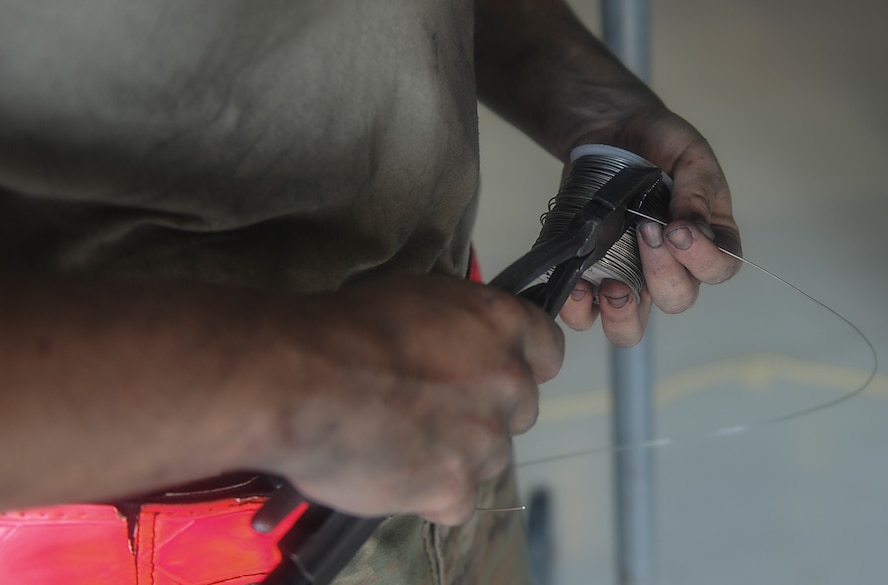 An aerospace propulsion journeyman with the 1st Special Operations Aircraft Maintenance Squadron cuts a length of wire while conducting maintenance on an AC-130U Spooky gunship engine at Hurlburt Field, Fla., July 6, 2017. Aerospace propulsion technicians test, maintain and repair AC-130U engines, preparing them to execute the mission any time, any place. (U.S. Air Force photo by Airman 1st Class Rachel Yates)