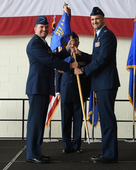 U.S. Air Force Col. David Owens, left, 317th Airlift Wing commander, hands a guidon to Col. James Hackbarth, 317th Operation Support Group commander, at Dyess Air Force Base, Texas July, 6, 2017. The 317th OSG was created in support of the newly activated 317th Airlift Wing. (U.S. Air Force photo by Senior Airman Alexander Guerrero)