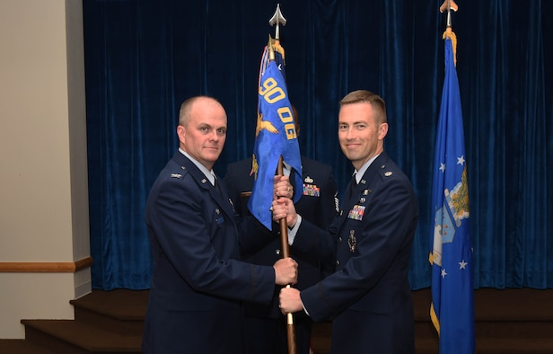 Col. Todd Sauls, 90th Operations Group commander, passes the guidon to Lt. Col. George Chapman, 320th Missile Squadron commander, during the 320th MS change of command ceremony at F.E. Warren Air Force Base, Wyo., July 5, 2017. The ceremony signified the transition of command from Lt. Col. Russell Williford. (U.S. Air Force photo by Airman 1st Class Breanna Carter)
