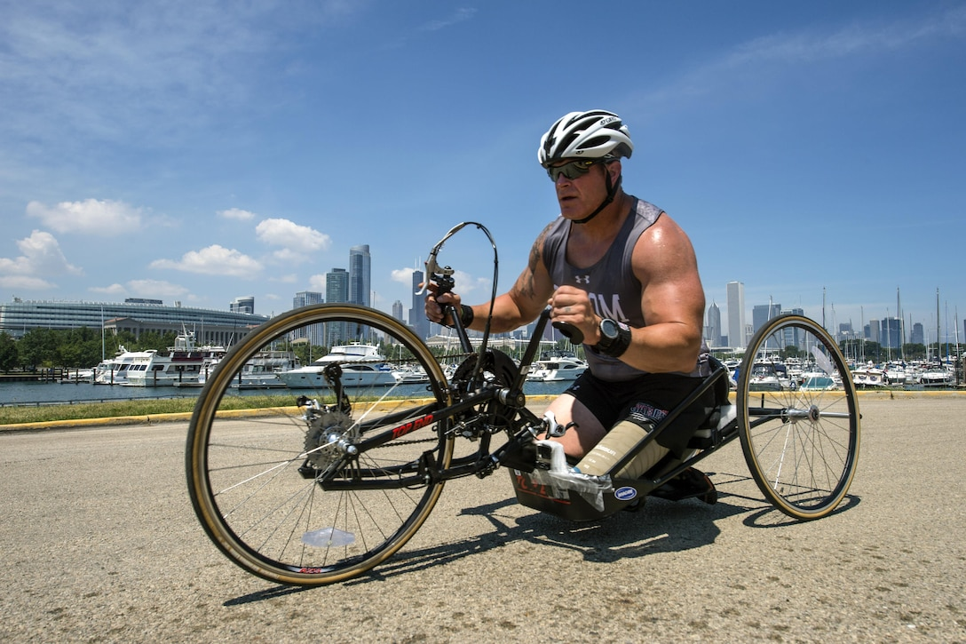 A soldier steers a handcycle with a Chicago skyline backdrop.