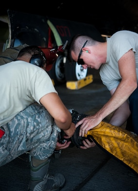 Staff Sgt. Charlie Hemstock, 9th Aircraft Maintenance Squadron crew chief, connects a hose to the U-2 Dragon Lady meant to pump cool air to the electronics to keep it from overheating while grounded at Beale Air Force Base, Calif., June 20, 2017. Maintaining the serviceability of the U-2 ensures Beal's readiness for worldwide intelligence, surveillance and reconnaissance missions. (U.S. Air Force photo by Airman 1st Class Justin Parsons/released)