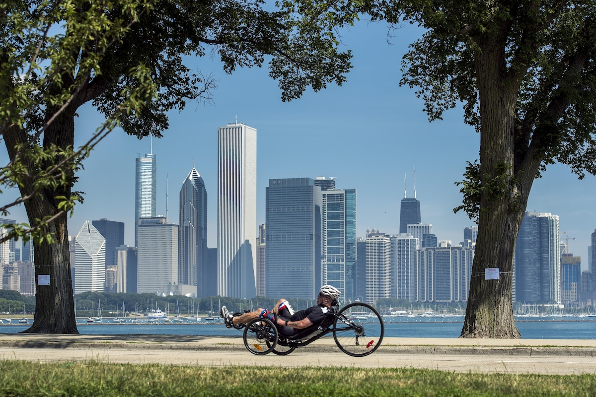 An airman races a recumbent cycle with the Chicago skyline in the background.