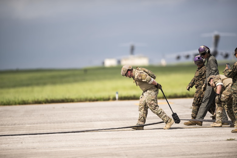 U.S. Air Force Staff Sgt. Patrick Skiles, 18th Logistics Readiness Squadron forward area refueling point team member, wrings out a refueling hose after FARP joint training exercise June 27, 2017, at Kadena Air Base, Japan. The training between services gave the Marine Corps a unique opportunity to practice joint operations with the 353rd Special Operations Group by utilizing the MC-130J Commando II and MC-130H Talon II's unique ability to air deliver 18th Logistics Squadron ground refueling operations to forward deployed locations. (U.S. Air Force photo by Senior Airman Omari Bernard)