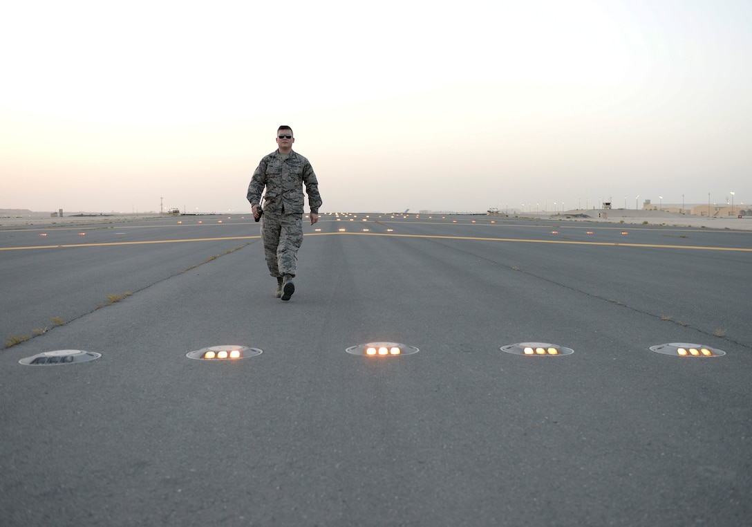U.S. Air Force Senior Airman William Terry, airfield management shift lead assigned to the 379th Expeditionary Office of Strategic Services, walks the runway at dusk during a lighting check at Al Udeid, Air Force Base, Qatar, June 22, 2017. Airfield Management oversees more than 20 million square feet of airfield at Al Udeid in addition to overseeing the airfield driving program and filing all flight plans for flights arriving to and departing from the base. (U.S. Air National Guard photo by Tech. Sgt. Bradly A. Schneider/Released)