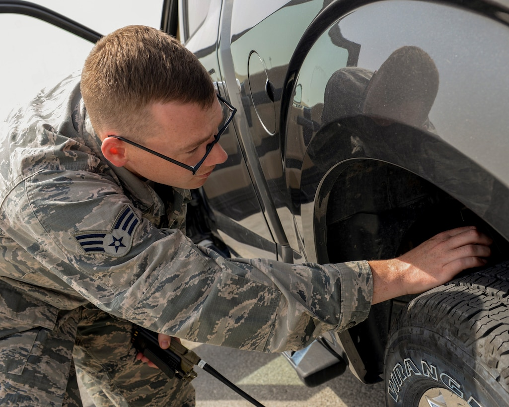 U.S. Air Force Senior Airman Thomas Smith, airfield management shift lead assigned to the 379th Expeditionary Office of Strategic Services, checks his vehicle's tire treads for debris by completing a foreign object damage (FOD) check prior to driving onto the runway at Al Udeid, Air Force Base, Qatar, June 7, 2017. Airfield Management oversees more than 20 million square feet of airfield at Al Udeid in addition to overseeing the airfield driving program and filing all flight plans for flights arriving to and departing from the base. (U.S. Air National Guard photo by Tech. Sgt. Bradly A. Schneider/Released)