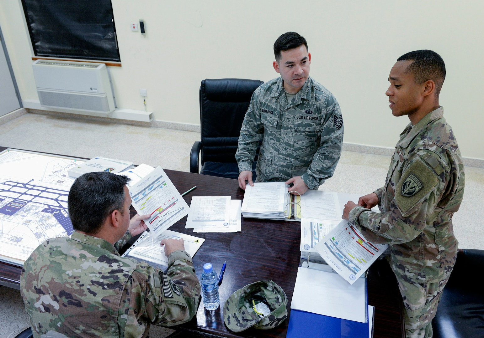U.S. Air Force Tech. Sgt. Santino Sustaita, airfield driving program manager assigned to the 379th Expeditionary Office of Strategic Services, center, reviews training material with airfield driving trainers at Al Udeid, Air Force Base, Qatar, June 7, 2017. Airfield Management oversees more than 20 million square feet of airfield at Al Udeid in addition to overseeing the airfield driving program and filing all flight plans for flights arriving to and departing from the base. (U.S. Air National Guard photo by Tech. Sgt. Bradly A. Schneider/Released)