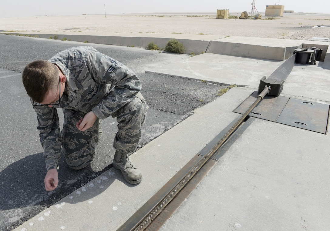 U.S. Air Force Senior Airman Thomas Smith, airfield management shift lead assigned to the 379th Expeditionary Office of Strategic Services, picks up small stones from the runway during a general runway inspection at Al Udeid, Air Force Base, Qatar, June 7, 2017. Airfield Management oversees more than 20 million square feet of airfield at Al Udeid in addition to overseeing the airfield driving program and filing all flight plans for flights arriving to and departing from the base. (U.S. Air National Guard photo by Tech. Sgt. Bradly A. Schneider/Released)