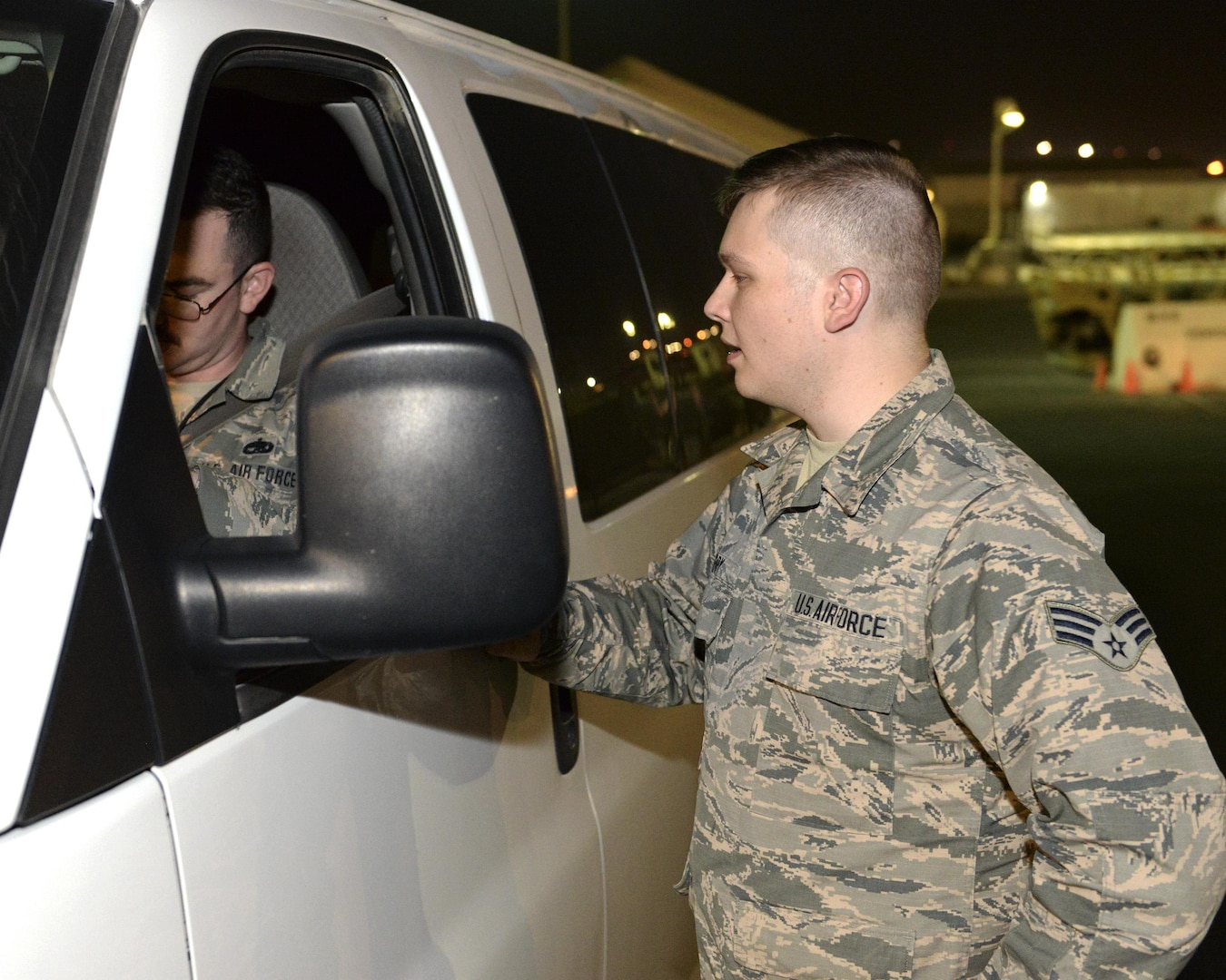 U.S. Air Force Senior Airman William Terry, airfield management shift lead assigned to the 379th Expeditionary Office of Strategic Services, asks to see an Airman's airfield drivers license during a random check conducted on the runway at Al Udeid, Air Force Base, Qatar, June 22, 2017. Airfield Management oversees more than 20 million square feet of airfield at Al Udeid in addition to overseeing the airfield driving program and filing all flight plans for flights arriving to and departing from the base. (U.S. Air National Guard photo by Tech. Sgt. Bradly A. Schneider/Released)
