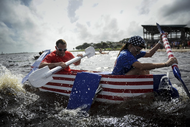 Capt. Conor Mulligan (left), the 1st Special Operations Force Support Squadron military personnel flight commander, and 2nd Lt. Taylor Pearson, a 1st SOFSS force support officer deputy, paddle to the finish line during the cardboard boat regatta at Hurlburt Field, Fla., June 24, 2017. Mulligan and Pearson won first place out of six other teams that competed in the race. (U.S. Air Force photo/Airman 1st Class Dennis Spain)