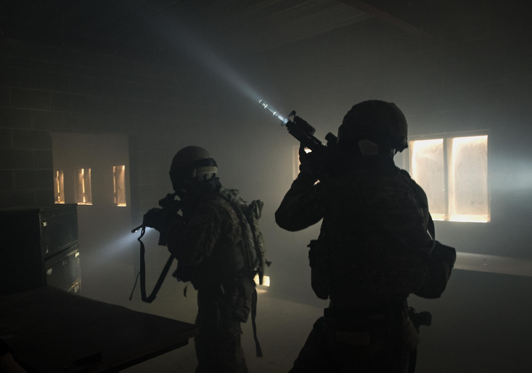 Airmen from the 822d Base Defense Squadron storm a building to rescue a simulated hostage rescue during the Scorpion Fire Team Challenge, June 28, 2017, at Moody Air Force Base, Ga. The challenge was designed to push the Airmen to their physical and mental limits by incorporating written tests, hostage rescues, blindfolded weapons assembly and physical exertion sessions among 14 other challenges. Eighteen four-person teams competed during the two-day event for various prizes and bragging rights. (U.S. Air Force photo/Senior Airman Janiqua P. Robinson)