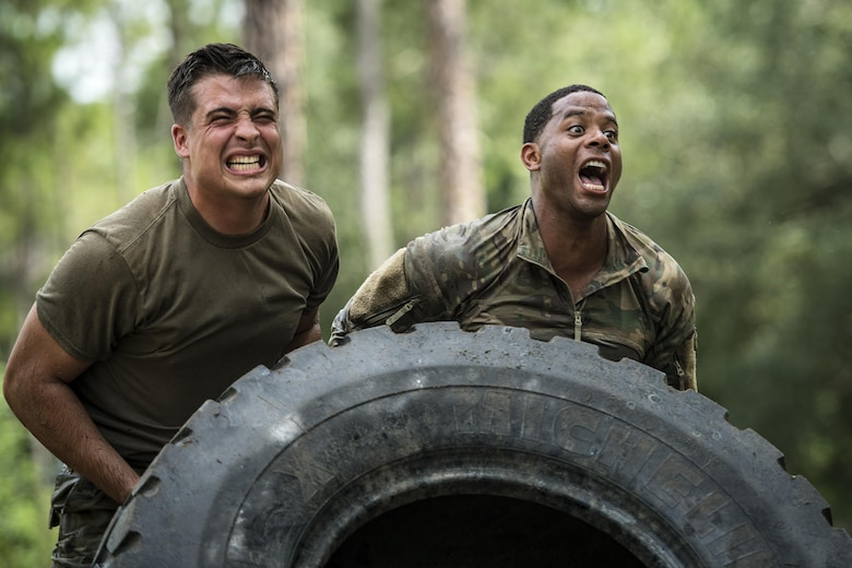 Airmen from the 822nd Base Defense Squadron flip a tire during the Scorpion Fire Team Challenge, June 29, 2017, at Moody Air Force Base, Ga. The challenge was designed to push the Airmen to their physical and mental limits, by incorporating written tests, hostage rescues, blindfolded weapons assembly and physical exertion sessions among 14 other challenges. Eighteen four-person teams competed during the two-day event for various prizes and bragging rights. (U.S. Air Force photo/Senior Airman Janiqua P. Robinson)