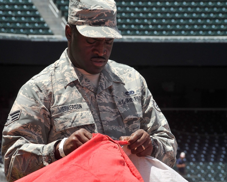 Senior Airman Antonio Merkerson, Air Transportation Journeyman for the 94th Aerial Port Squadron at Dobbins Air Reserve Base, clips an enormous American flag together at SunTrust Park in Atlanta, Georgia. A group of about 80 men and women from the Army, Georgia National Guard, Air National Guard and Air Force Reserve volunteered to help unfurl the flag during the Atlanta Braves game on July 4. (U.S. Air Force photo by Staff Sgt. Jaimi L. Upthegrove)