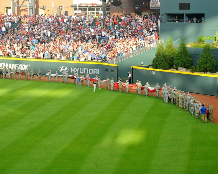 A group of about 80 men and women from the Army, Georgia National Guard, Air National Guard and Air Force Reserve line up holding an enormous United States-shaped American Flag at SunTrust Park in Atlanta, Georgia. The group volunteered to unfurl the flag during the opening ceremony of the Atlanta Braves game on July 4, 2017. (U.S. Air Force photo by Staff Sgt. Jaimi L. Upthegrove)