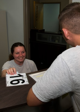 Senior Airman Courtney Sire, Fitness Assessment Cell physical training leader, hands an Airman their test number at the McAdoo Fitness Center on Minot Air Force Base, N.D., June 28, 2017. Squadron or unit PTLs can be assigned to FAC duty for a month. (U.S. Air Force photo by Airman 1st Class Alyssa M. Akers)