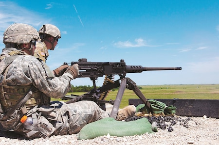 Spc. Jeremy Furr, a Soldier with Headquarters and Headquarters Troop, 180th Cavalry Regiment, 45th Infantry Brigade Combat Team, fires an M2 .50 caliber machine gun during an annual training exercise at Fort Riley, near Junction City, Kansas, June 21. As his assistant gunner, Spc. Stephen Gauthier, a Soldier with Headquarters and Headquarters Troop, 180th Cavalry Regiment, gives his gunner direction in order to more effectively hit the target.