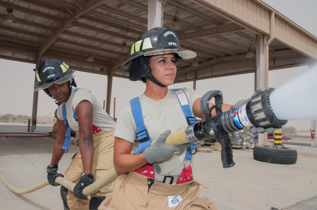Staff Sgt. Jessica Mendoza (right) operates a hand line with assistance from Senior Airman Christa Dennis at one of the 386th Air Expeditionary Wing's fire stations an undisclosed location in Southwest Asia, June 25, 2017. Mendoza and Dennis are firefighters assigned to the 386th Civil Engineer Squadron.(U.S. Air Force photo by Master Sgt. Eric M. Sharman)
