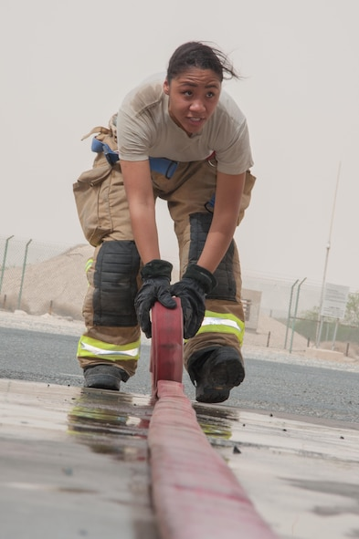 Senior Airman Ayanna Gaskin, a firefighter assigned to the 386th Civil Engineer Squadron, rolls a fire hose prior to storage  in the fire truck parking area at an undisclosed location in Southwest Asia, June 25, 2017. (U.S. Air Force photo by Master Sgt. Eric M. Sharman)