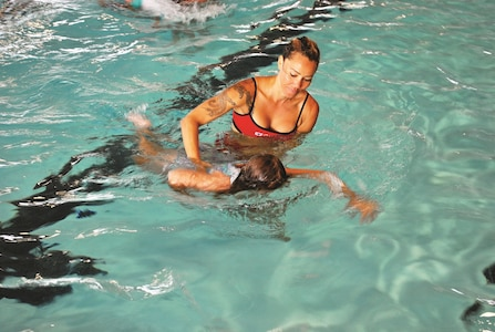 Tatiana Ferracioli da Silva, lifeguard and wife of Sgt. 1st Class Michael Mayo, 1st Squadron, 6th Cavalry Regiment, 1st Combat Aviation Brigade, 1st Infantry Division, assists Claire Shattuck, daughter of Warrant Officer 1 Yancy Shattuck, Headquarter and Headquarters Battalion, 1st Infantry Division, as she swims underwater during the World's Largest Swim Lesson June 22 at Eyster Pool.