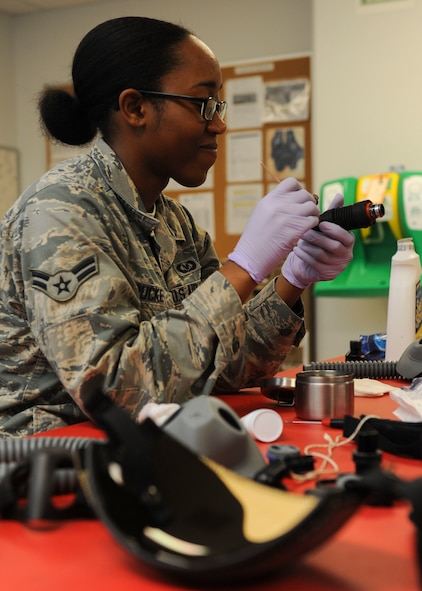 Airman 1st Class Shaquita Puckett, 5th Operations Support Squadron aircrew flight equipment technician, cleans a CRU-60/P connector at Minot Air Force Base, N.D., June 29, 2017. The CRU-60/P connects the aircraft oxygen supply-hose to aircrew members' breathing masks. (U.S. Air Force Photo by Airman 1st Class Jessica Weissman)