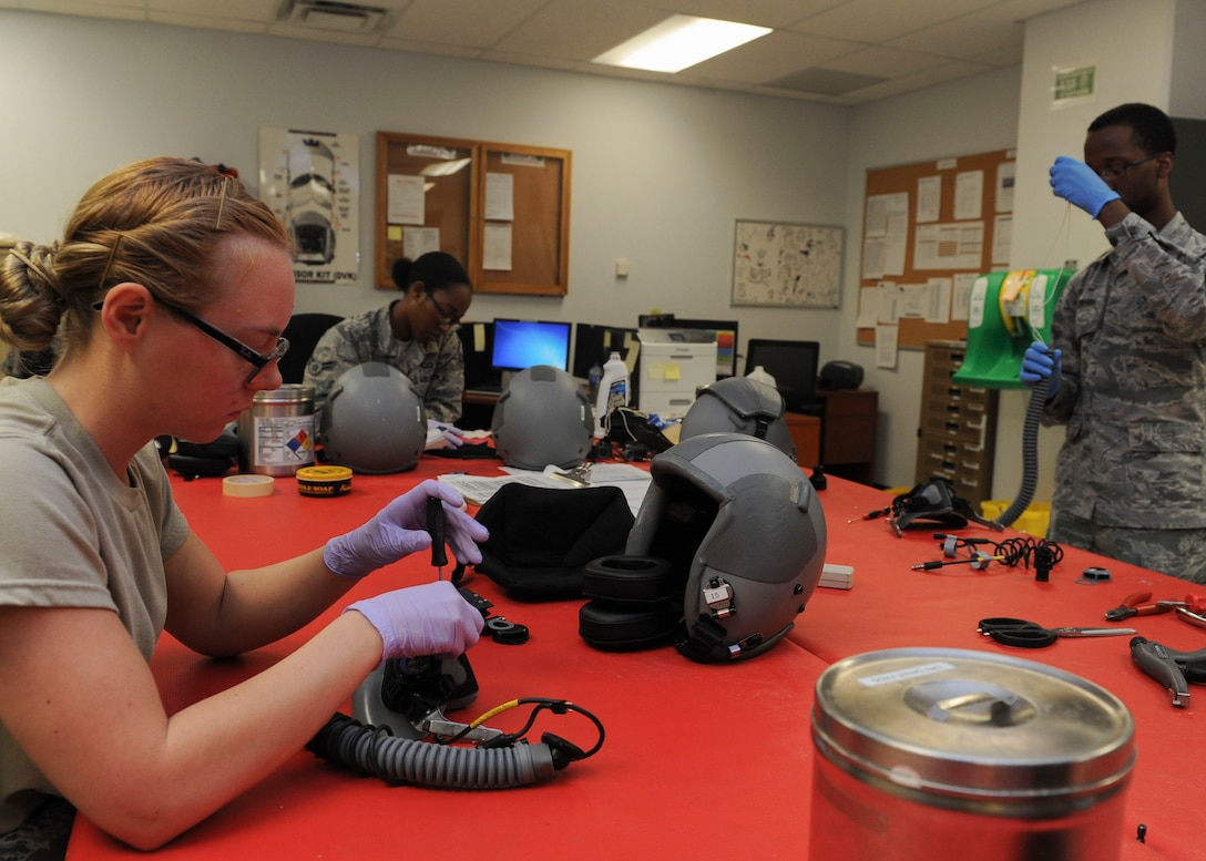 Members of the 5th Operations Support Squadron aircrew flight equipment helmet section assemble and inspect helmets at Minot Air Force Base, N.D., June 29, 2017. These technicians ensure helmets and oxygen masks are cleaned, inspected and assembled correctly. (U.S. Air Force Photo by Airman 1st Class Jessica Weissman)