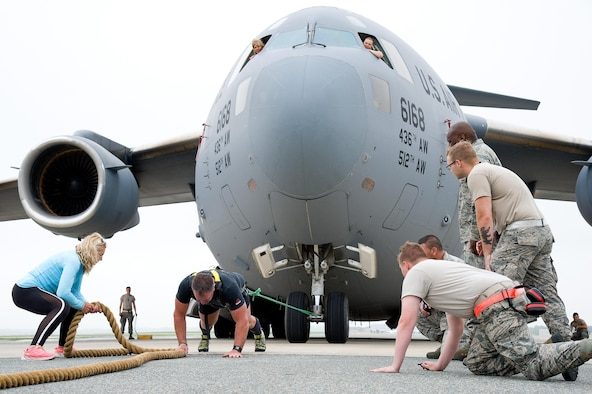 "From the flight deck, Master Sgt. Christine King, top left, and Tech. Sgt. Brinnae Wigley, top right, both 712th Aircraft Maintenance Squadron crew chiefs, watch Cmdr. Grant Edwards, Australian Federal Police, Embassy of Australia, Washington, D.C., repositions himself on his third attempt at pulling a C-17 Globemaster III weighing approximately 418,898 pounds, June 16, 2017, on Dover Air Force Base, Del. Kate Lord, Edwards' wife, left, and members of the 736th Aircraft Maintenance Squadron cheer on Edwards, an Australian strongman athlete, during this attempt. Edwards is scheduled to attempt pulling a C-17 during the ""Thunder Over Dover: 2017 Dover AFB Open House,"" Aug. 26-27. (U.S. Air Force photo by Roland Balik)"