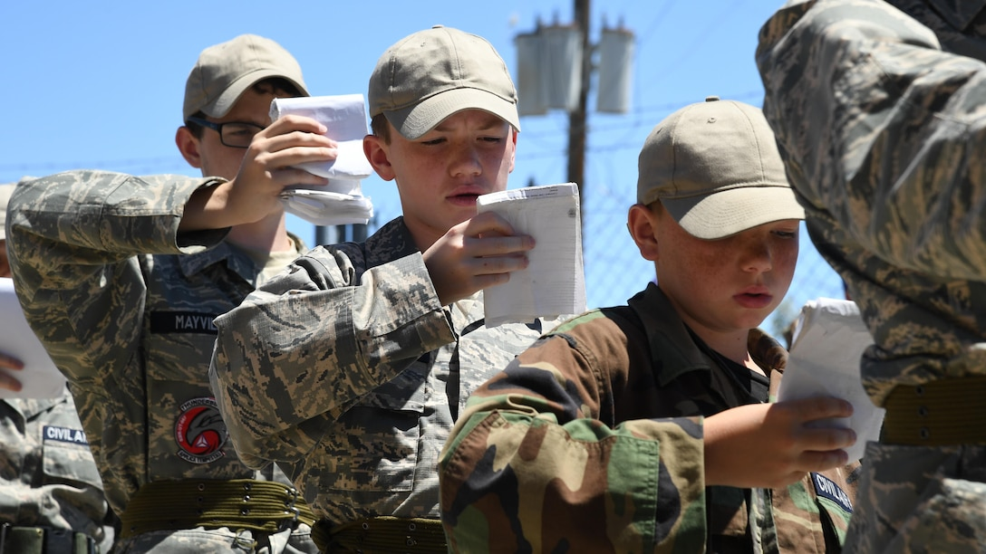 "Civil Air Patrol cadets review their ""smart books"" while standing in line during the Desert Hawk XV encampment, Historic Wendover Airfield, Utah. (U.S. Air Force photo/R. Nial Bradshaw)"