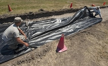 From left, Airman 1st Class Christopher Schroeder and Senior Airman Thomas Clark, 5th Civil Engineer Squadron pavements and equipment technicians, cover geotextile over the ground at Minot Air Force Base, N.D., June 12, 2017. Geotextiles are permeable fabrics used in conjunction with soil to separate, filter, reinforce, protect and drain water. (U.S. Air Force photo by Airman 1st Class Jonathan McElderry)