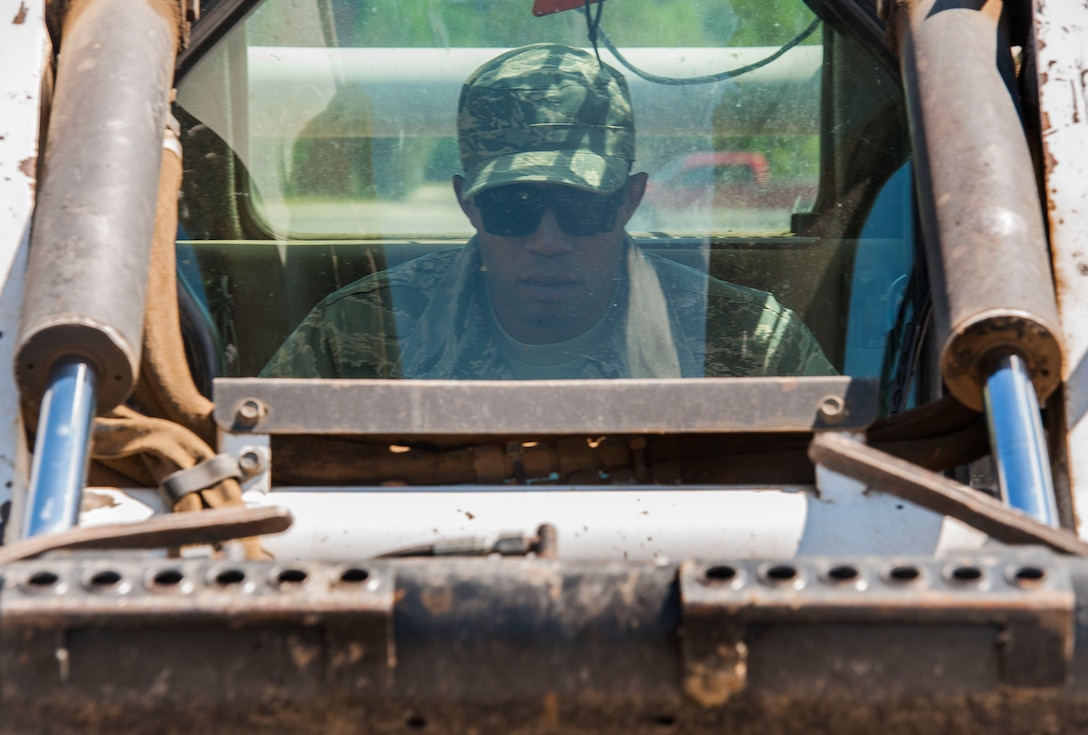 Airman 1st Class Harold McIntyre, 5th Civil Engineer Squadron pavements and equipment technician, operates a loader at Minot Air Force Base, N.D., June 12, 2017. After assessing which sections of sidewalk needed to be removed, the CES Airmen made relief cuts to the cracked concrete before replacing it. (U.S. Air Force photo by Airman 1st Class Jonathan McElderry)