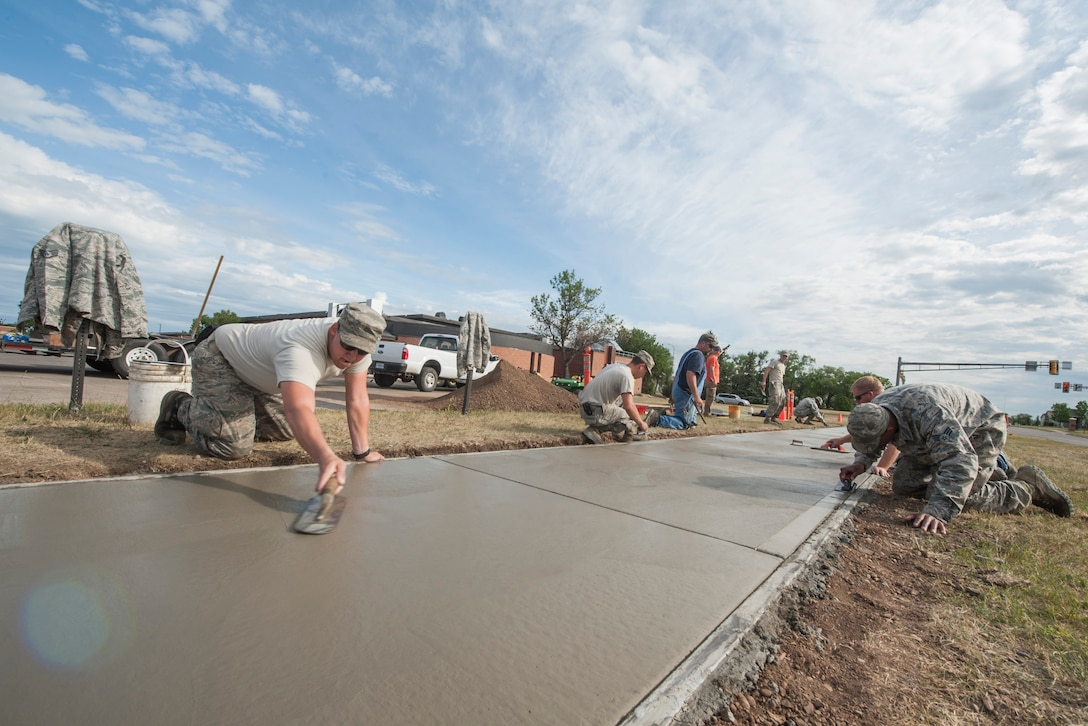Members of the 5th Civil Engineer Squadron flatten concrete for a sidewalk at Minot Air Force Base, N.D., June 29, 2017. CE Airmen use various equipment when remodeling the sidewalk, from fresno trowels to curing compounds. (U.S. Air Force photo by Airman 1st Class Jonathan McElderry)