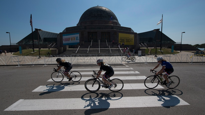 Athletes ride past Adler Planetarium during the cycling competition for the 2017 Department of Defense Warrior Games in Chicago, Ill., July 6, 2017. The annual games allow wounded, ill and injured service members and veterans to compete in paralympic-style sports including archery, cycling, field, shooting, sitting volleyball, swimming, track and wheelchair basketball. DoD photo by Roger L. Wollenberg