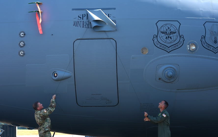 Col. Daniel Morgan, Joint Base Lewis-McChord installation commander, and Col. Leonard Kosinski, 62nd Airlift Wing commander, unveil the new name of a C-17 Globemaster III July 5, 2017, at Joint Base Lewis-McChord, Wash. The Spirit of Joint Base Lewis-McChord, tail number 10-0220 is newest C-17 of McChord's permanently assigned C-17 fleet. (U.S. Air Force photo/Senior Airman Jacob Jimenez)