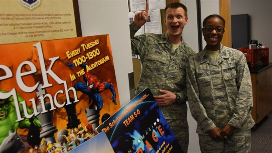 Chaplain (Capt.) Portmann Werner and Chaplain (Capt.) Jennifer Ray, 50th Space Wing Chaplain's Office, stand by various posters promoting 50 SW Chaplain programs at Schriever Air Force Base, Colorado, Monday, March 27, 2017. The office earned numerous awards for its service at Schriever, both on the Major Command and Air Force level. (U.S. Air Force photo/Airman 1st Class William Tracy)